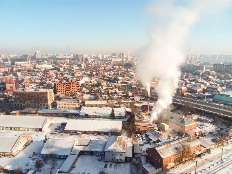 冬天镇 冷淡的晴天在城市 下雪在街道和烟上从锅炉上升 霜和太阳,一美妙的天 库存照片