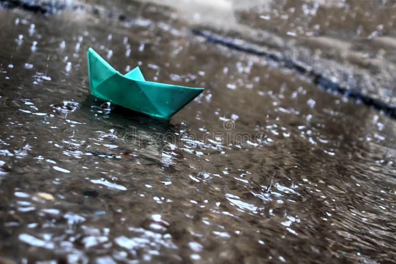冬天雨在以色列,洪水 雨水小河运载纸小船 免版税库存照片