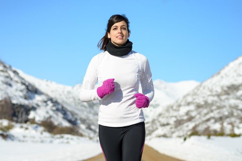 冬天雪女性运动员运行中 库存照片