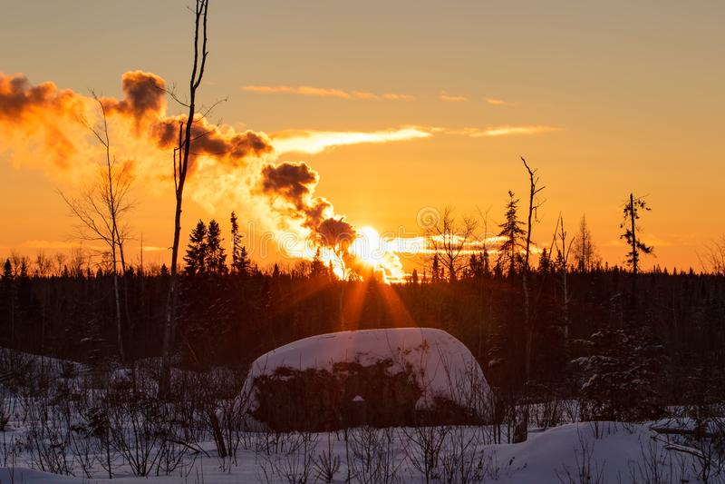 冬天风景日落和烟在冬天安大略加拿大 免版税库存照片