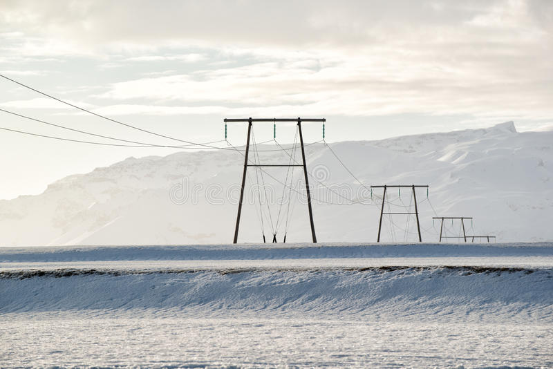 冬天风景,在一个多雪的领域由山,冰岛的输电线 库存图片