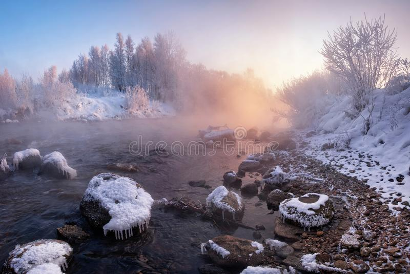 冬天风景:河流动在积雪和冰川覆盖的石头中的和罗斯升起在森林带淡红色的W的太阳 免版税图库摄影