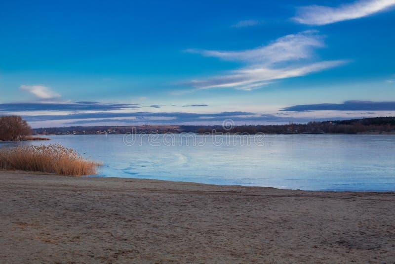 冬天黄昏日落paysage风景冰了冻河海滩 免版税库存图片