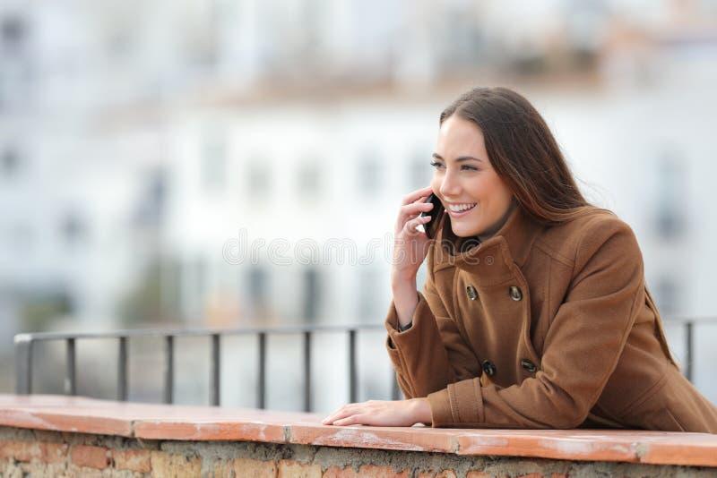 冬天,快乐的女人在阳台上打电话 免版税库存图片
