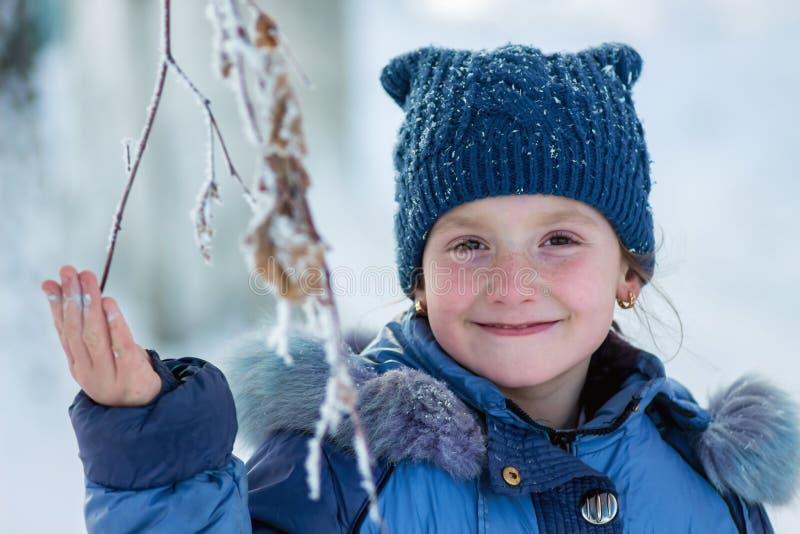 冬天,拿着tree_的一个冻结的分支的愉快的微笑的女孩 免版税库存照片