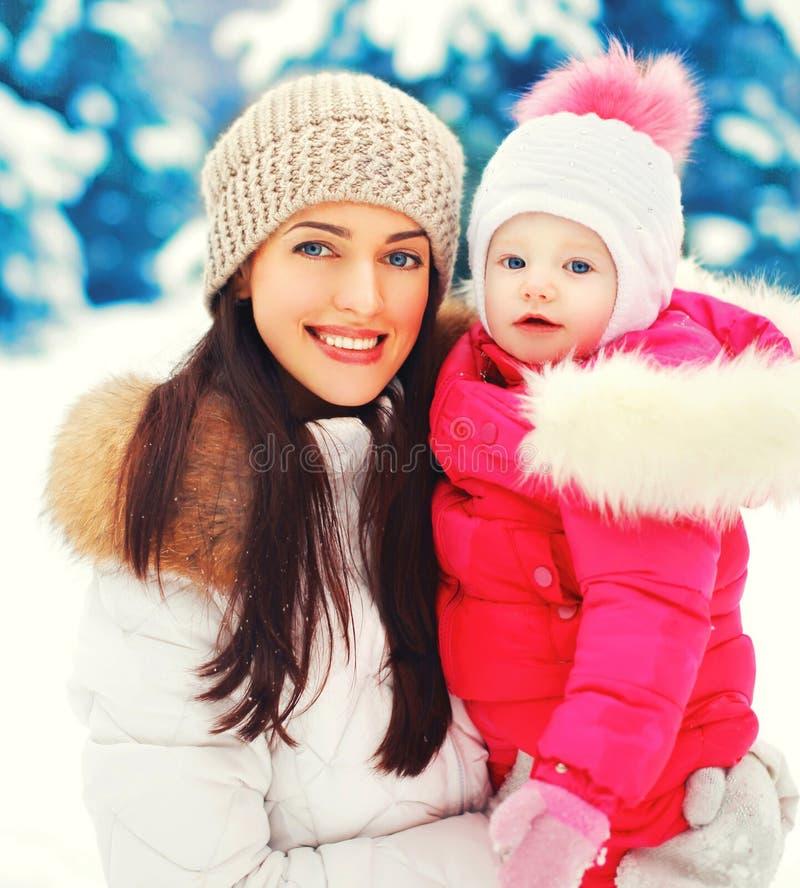 冬天画象愉快的微笑的母亲和婴孩移交多雪的圣诞树 免版税库存图片