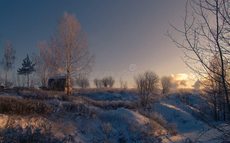 冬天` s传说 小山的议院在冬天下午的日落 免版税库存图片