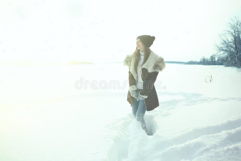 冬季体育活动 步行与背包和雪靴的妇女徒步旅行者snowshoeing在雪足迹森林 库存图片