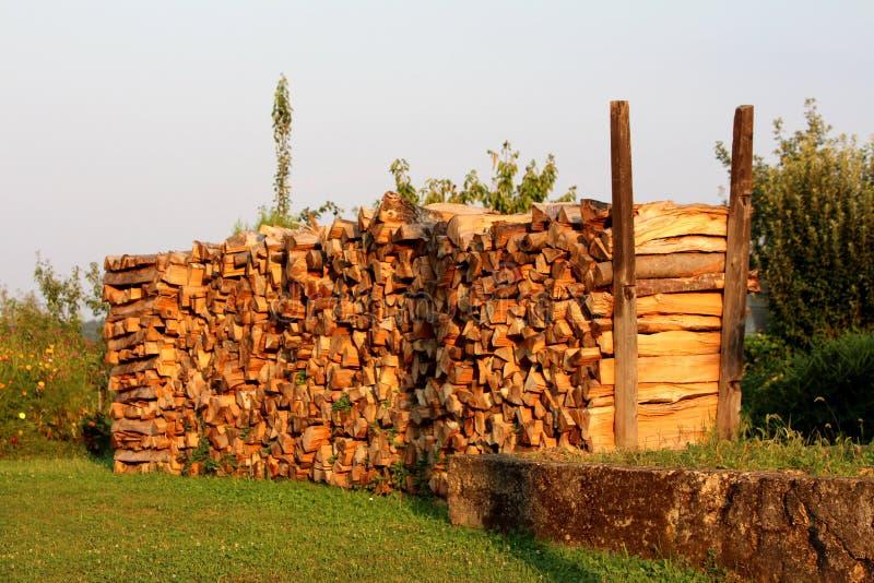 冬季木柴准备的堆在后院包围与新近地被剪的草和花在温暖的好日子在日落 库存图片