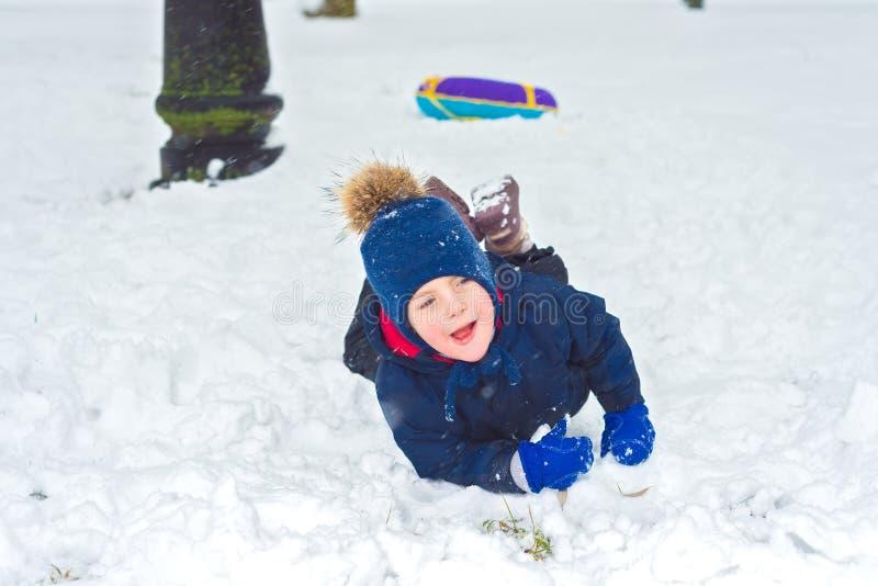 冬季衣服和帽子的小男孩落入雪 免版税库存照片