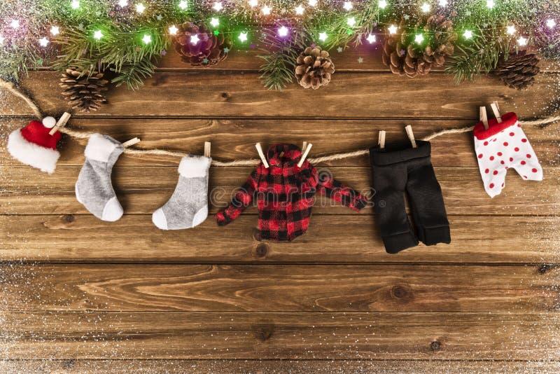 冬季衣服垂悬 树枝和一张木桌在背景中 免版税库存照片