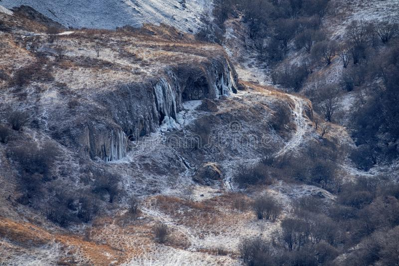 冬季,带露台、灌木、溪流和冻瀑布的沟壑 库存图片