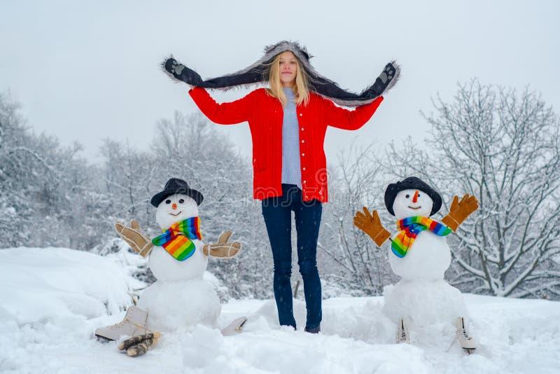 冬日女孩做雪人 户外圣诞快乐的人 女人做雪人和冬日乐 库存照片
