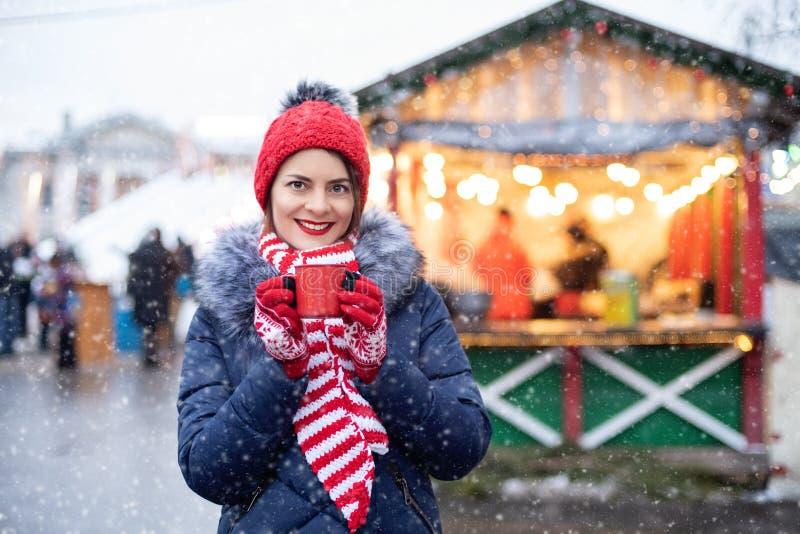 冬雪天在户外喝热咖啡的红帽可爱女孩 站在街上喝热 免版税库存图片