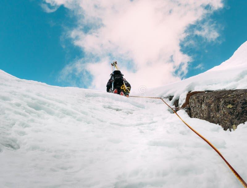 冰上升:雪和岩石duri一条混杂的路线的登山家  免版税库存图片