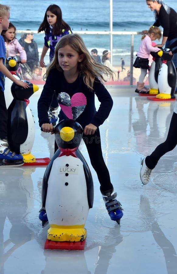 滑冰与在Bondi滑冰场的企鹅冰鞋援助的女孩 免版税图库摄影