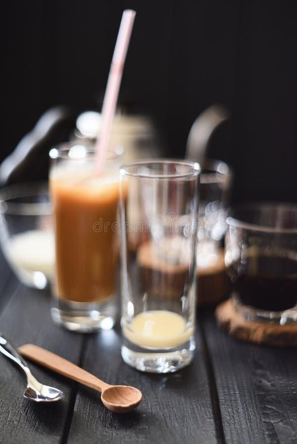 冰冻咖啡用在高玻璃的浓缩牛奶在黑背景 免版税库存图片