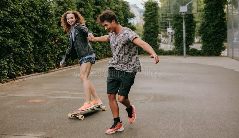 滑冰在与朋友的一个篮球场的妇女 库存图片