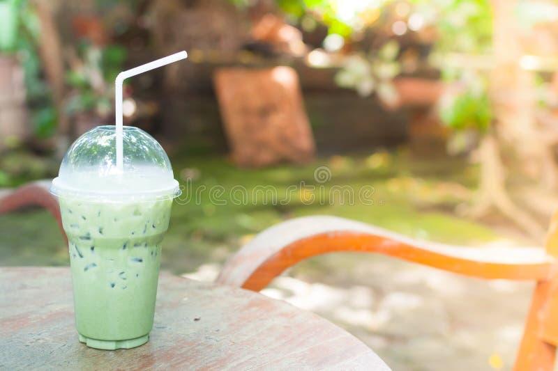 冰在塑料杯子的绿茶在表上 库存图片