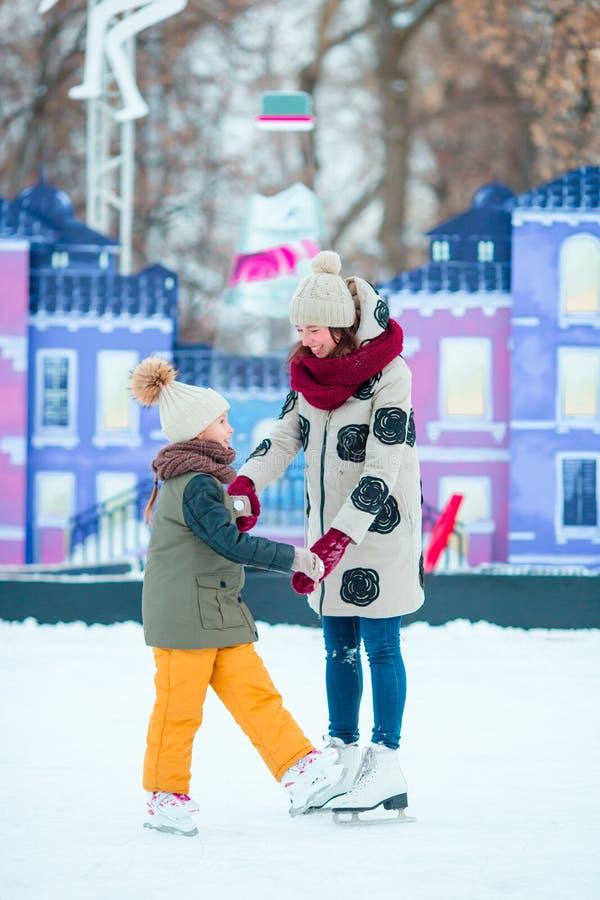 滑冰在有母亲的冰溜冰场的小可爱的女孩 免版税库存图片