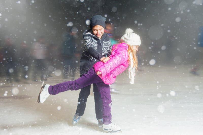 滑冰在滑冰场,冬天夜的愉快的孩子 免版税库存图片