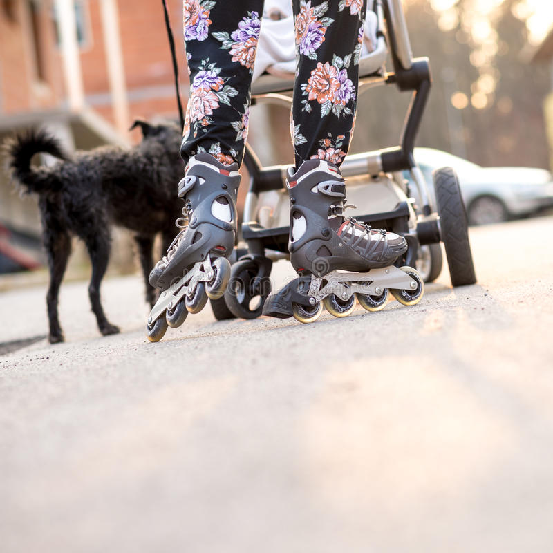 滑冰妇女佩带的直排轮式溜冰鞋,当推挤婴儿车时 免版税库存照片
