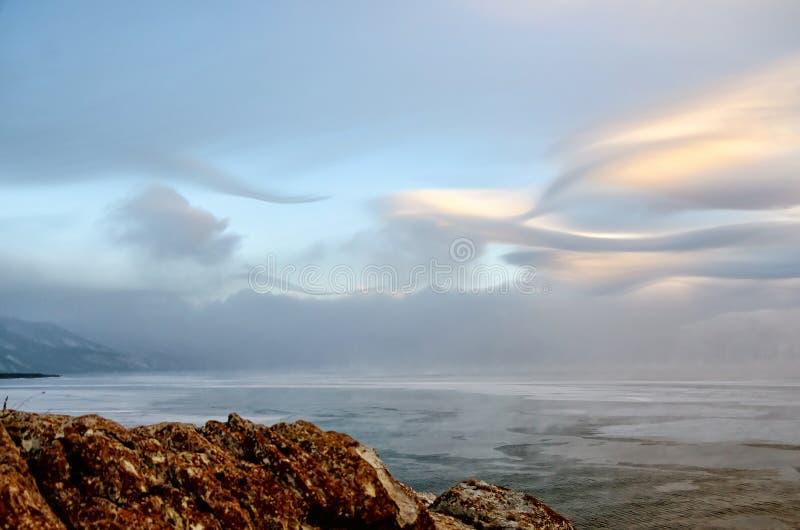 冰小丘和岩石的领域在冻贝加尔湖 日落 免版税库存图片