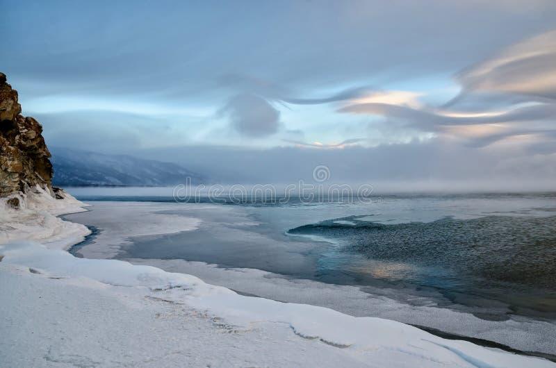 冰小丘和岩石的领域在冻贝加尔湖 日落 库存图片