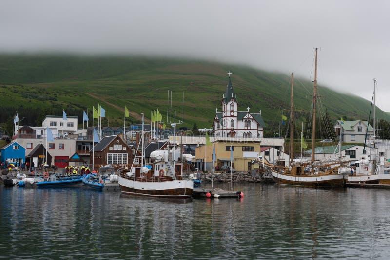 冰岛海口:小船钓鱼的和鲸鱼观看的游览的会集在胡萨维克港  免版税库存图片