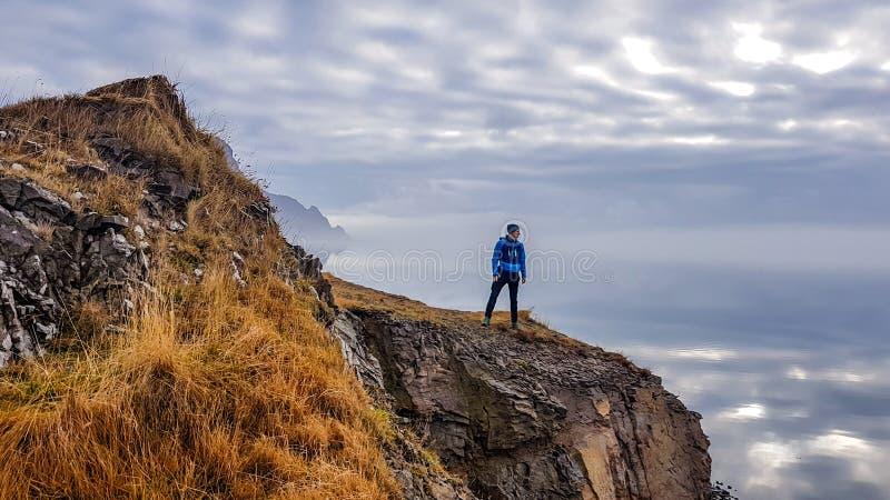 冰岛-在峭壁的年轻人身分与不尽的天际 库存照片