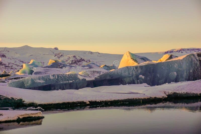 冰巨大的大块在冰河湖的与反射的日落的在水中 库存照片