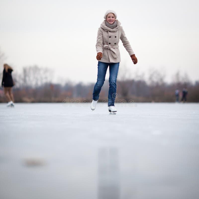 滑冰户外在池塘的少妇 免版税库存照片