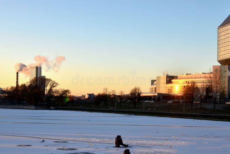 冰抓住鱼的渔夫在日落的背景的一条冻河 免版税图库摄影