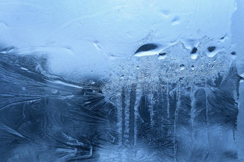 冰样式和冻结的水下落在冬天玻璃窗 库存照片