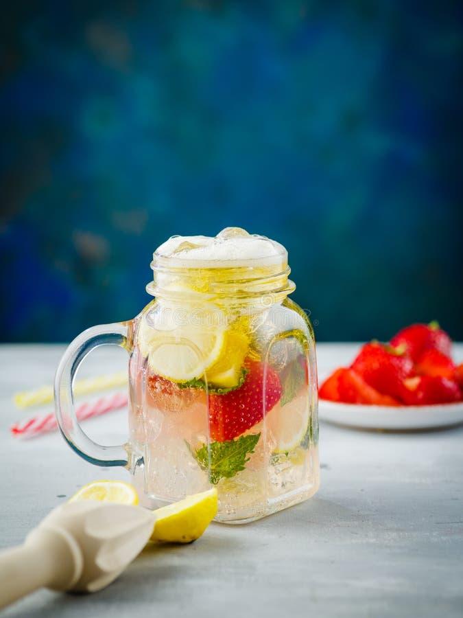 冰泡沫腾涌的草莓柠檬水用薄菏和柠檬在金属螺盖玻璃瓶 免版税库存图片