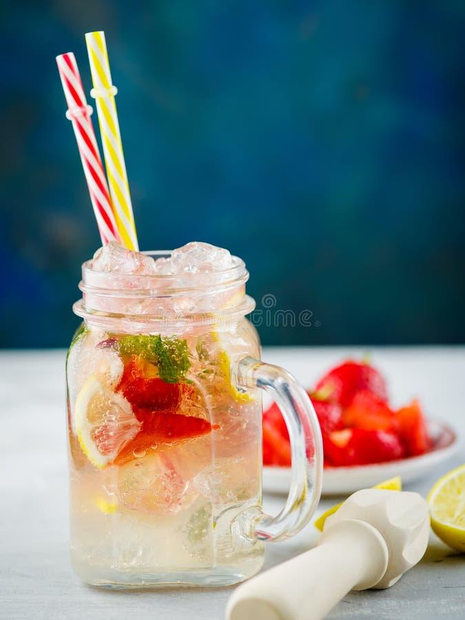 冰泡沫腾涌的草莓柠檬水用薄菏和柠檬在金属螺盖玻璃瓶 库存图片