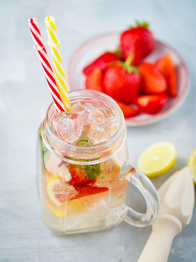 冰泡沫腾涌的草莓柠檬水用薄菏和柠檬在金属螺盖玻璃瓶 免版税库存照片