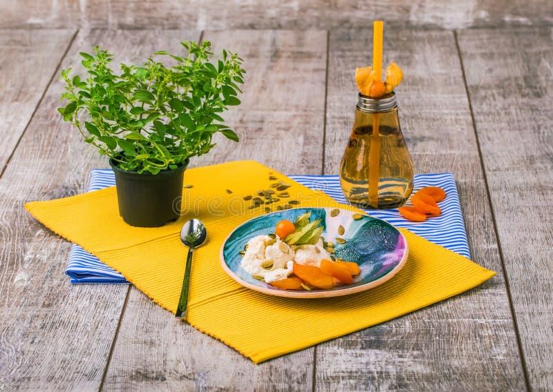 冰淇凌板材、橙色瓶和一棵绿色中国植物的明亮的构成 在木的一套逗人喜爱的餐具 图库摄影