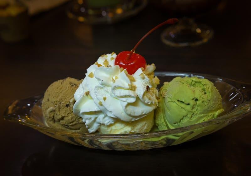 冰淇淋三个瓢与打好的奶油和樱桃的 库存图片