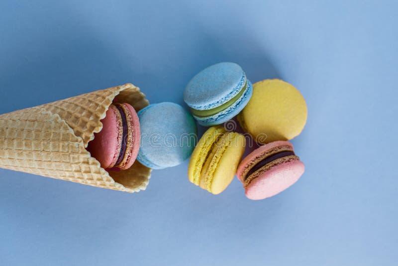 冰淇淋与五颜六色的macaron的奶蛋烘饼在蓝色淡色背景顶视图的锥体或蛋白杏仁饼干 五颜六色的糖果颜色 甜 免版税图库摄影
