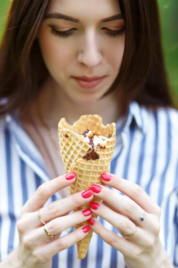 冰淇淋特写镜头 有拿着冰淇淋的长的流动的头发的年轻美女 免版税库存图片