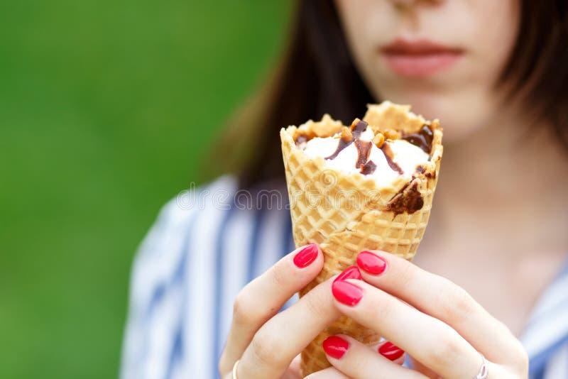 冰淇淋特写镜头 有拿着冰淇淋的长的流动的头发的年轻美女 库存图片
