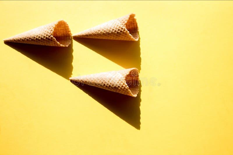 冰淇淋的三个空的奶蛋烘饼杯子在黄色背景在明亮的阳光和酥脆,坚硬阴影下 r 图库摄影
