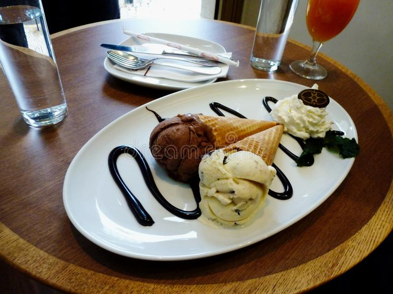 冰淇淋锥体服务在白色板材和用熔化chockolate动机和绿色薄荷的叶子装饰在圆的餐馆桌上 库存图片