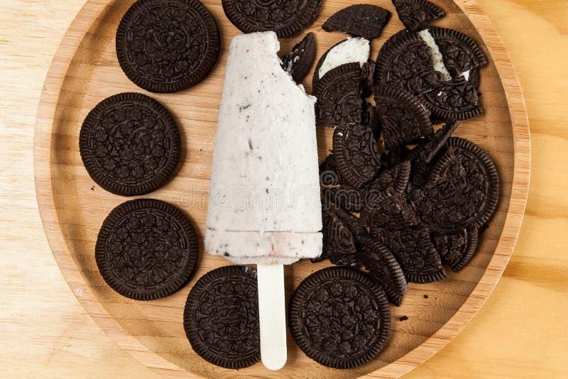 冰淇淋-鲜美和刷新的冰棍儿调味了曲奇饼和奶油,在木背景的照片 库存图片