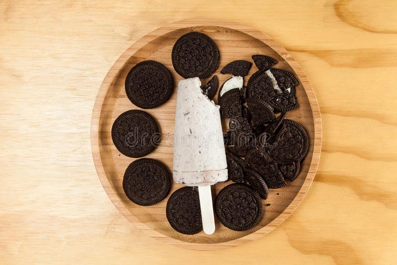 冰淇淋-鲜美和刷新的冰棍儿调味了曲奇饼和奶油,在木背景的照片 免版税库存照片