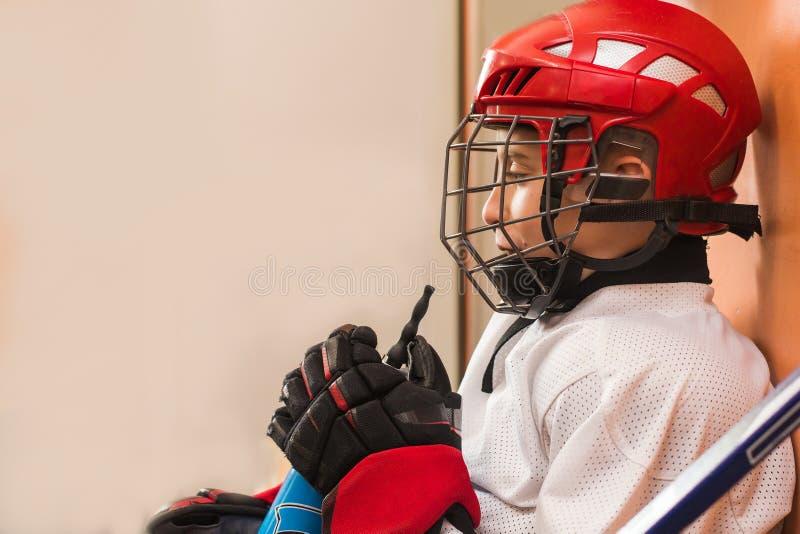冰球制服的年轻男孩 免版税库存图片