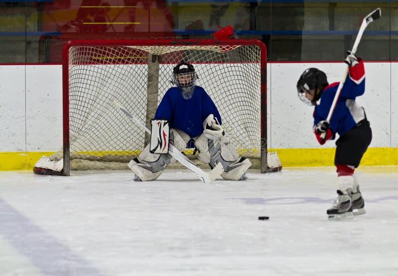 冰球球员射击顽童在网 免版税图库摄影