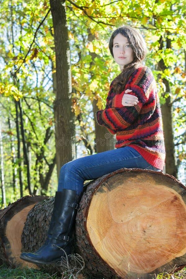 结冰的妇女坐被锯的树干和拥抱 免版税图库摄影