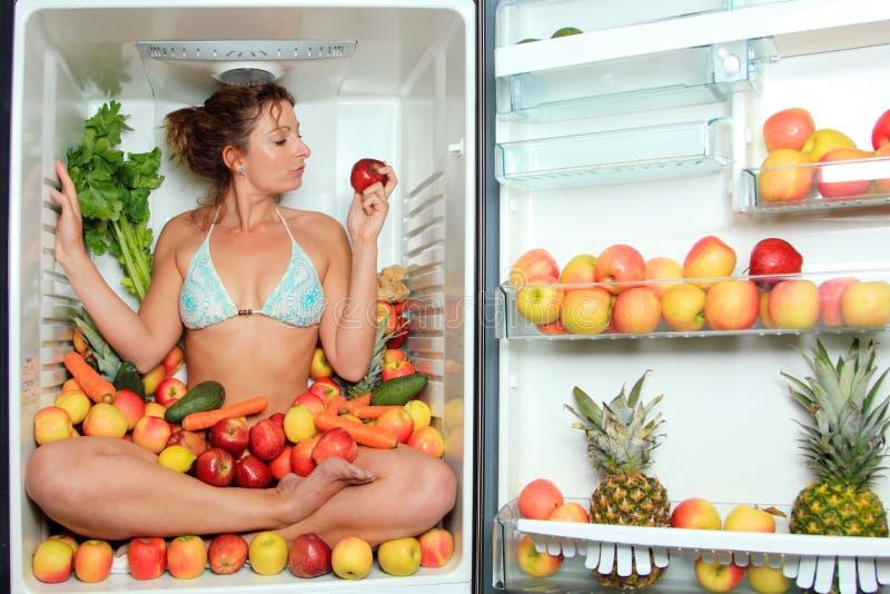 冰箱坐的妇女 免版税库存照片
